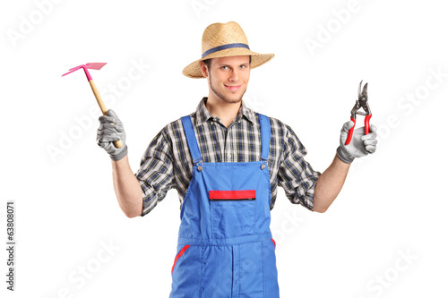 Male gardener holding working tools