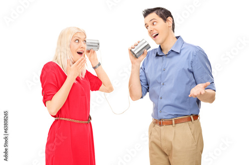 Man and woman talking through a tin can phone