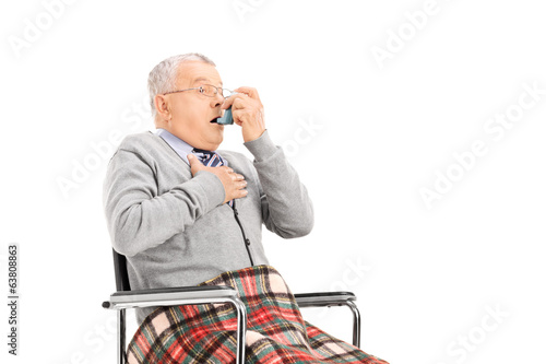 Senior man breathing through his inhaler
