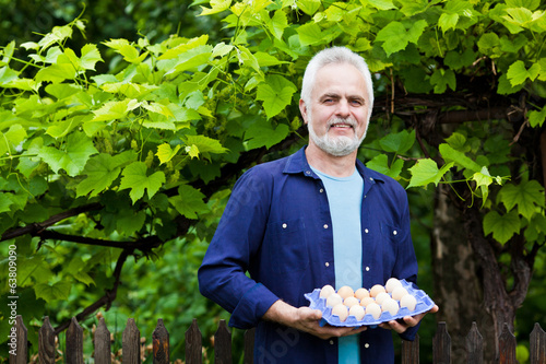 Happy young man holding his chicken and basket of eggs in his ga