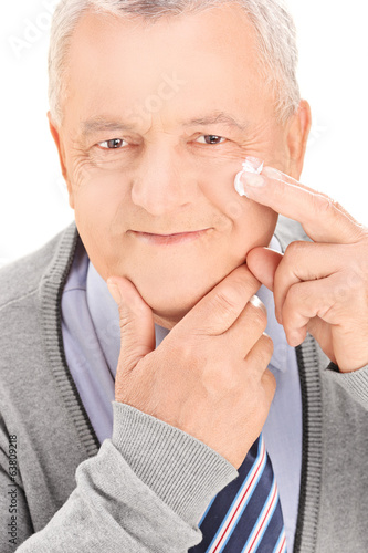 Senior man putting shaving cream on