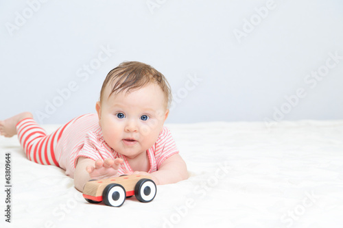 cute little girl reaching car toy