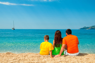 Happy family: Mom, Dad and son sitting on the beach.