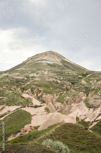 Lonely mountain with rock formations on its slope