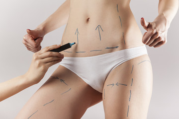 Female body with the drawing arrows on it isolated on white. Fat