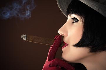 beautiful fashionable woman smokes a cigar