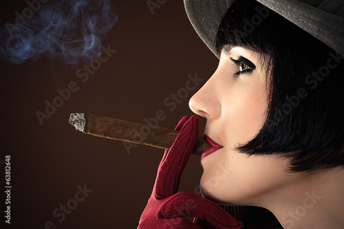 beautiful fashionable woman smokes a cigar