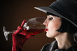 beautiful woman in a hat drinking wine