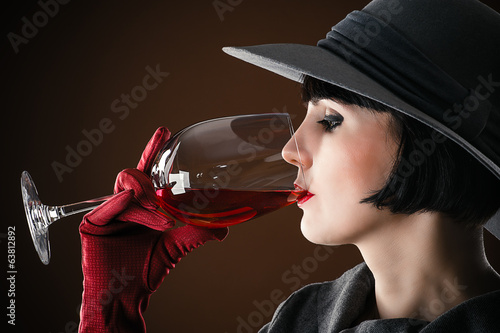 beautiful woman in a hat drinking wine