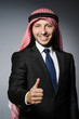 Arab businessman with thumbs up againt grey background