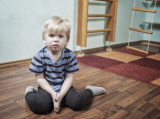 Sad boy in children room