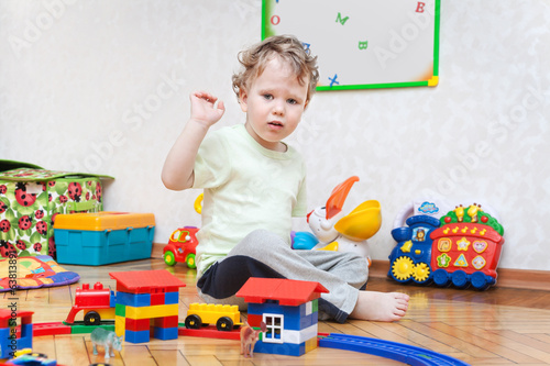Cute playing boy in children room