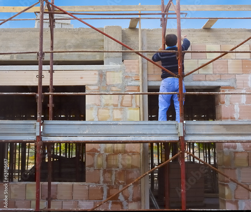 Worker on scaffold building masonry clay blocks