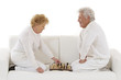 senior couple sitting on couch playing chess