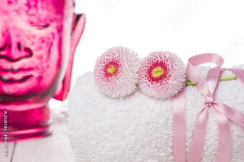 towel with flowers and glass Buddha, spa, isolated
