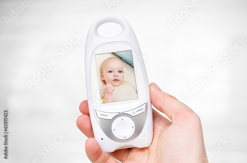 Hand holding video baby monitor for security of the baby