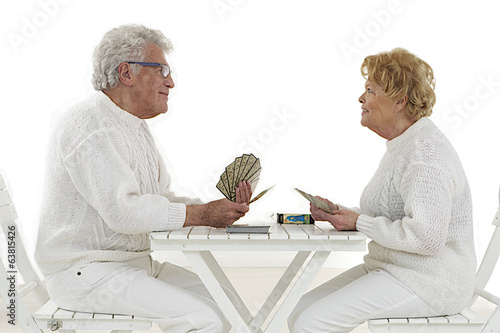 Happy old couple playing together with cards