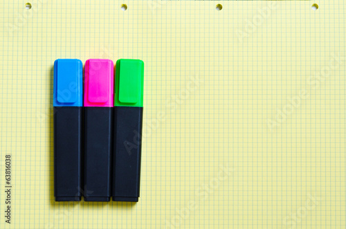 colored markers lie on a sheet of notebook