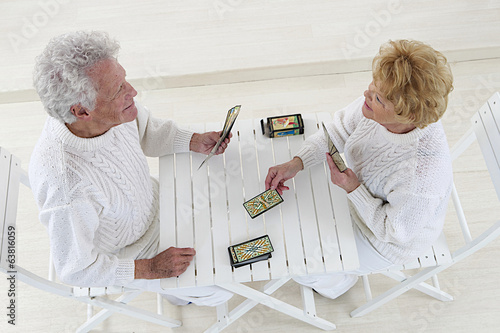 top view of an happy old couple playing together with cards