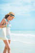 Young woman in hat with bag walking at seaside