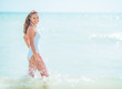 Happy young woman in swimsuit standing in sea