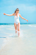 Happy young woman in swimsuit walking on sea shore