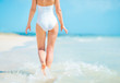 Closeup on young woman in swimsuit walking on sea coast