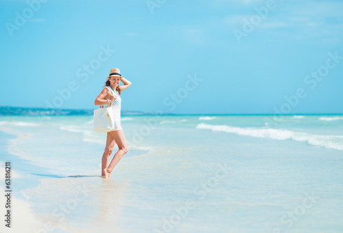 Young woman in hat with bag on sea shore
