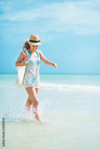 Young woman in hat with bag playing with waves at seaside