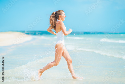 Happy young woman in swimsuit running into sea