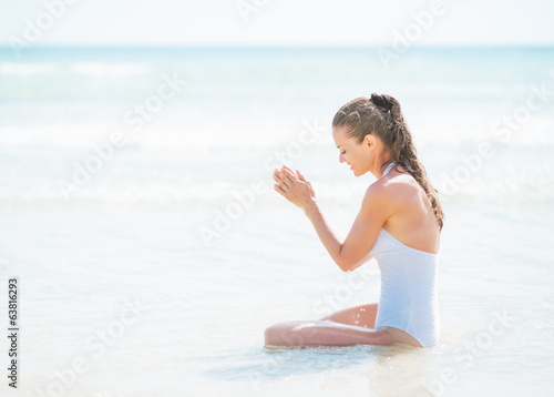 Happy young woman in swimsuit sitting at seaside
