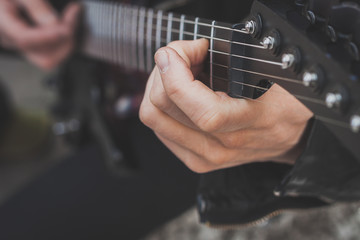 Detail of fingers playing electric guitar