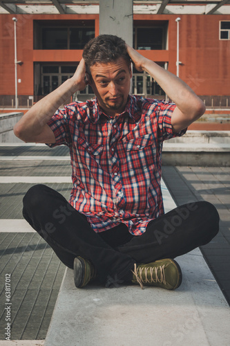 Man in short sleeve shirt sitting outdoor