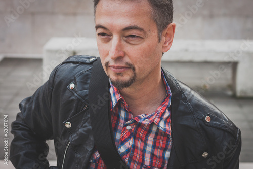 Portrait of a man in black leather jacket playing guitar