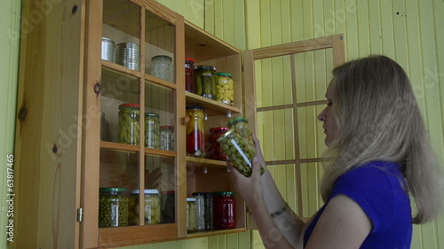 Lady take glass jar with canned olive and mushrooms from cabinet