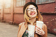 Cheerful woman in the street drinking morning coffee in sunshine - 63817670