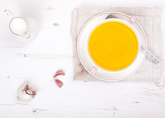 Top view of spiced carrot soup in a bowl, on the white table