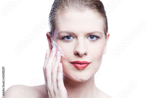 Close up of female face applying face cream isolated on white
