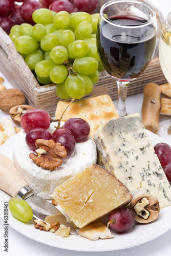 assortment of cheeses, glass of red wine, grapes, crackers