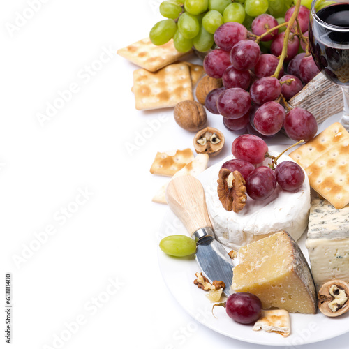 assortment of cheeses, glass of red wine, grapes and crackers