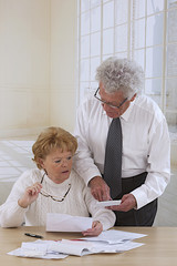 comfortable.senior couple at home organizing  bills and paper