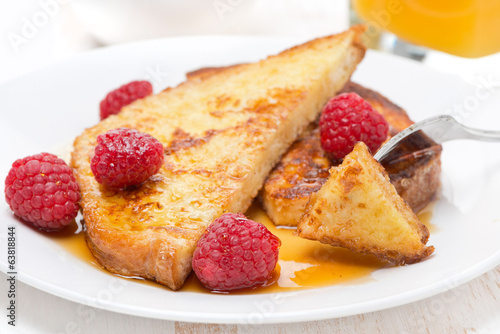 French toast with raspberries and maple syrup on a plate
