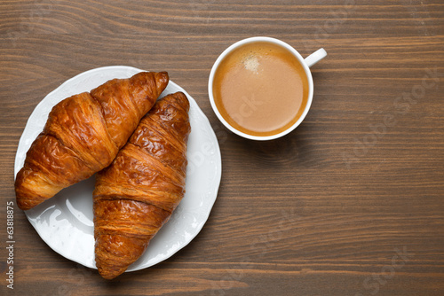 fresh croissants, cup of espresso on wooden background