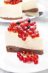 piece of cheesecake decorated with red and black currants