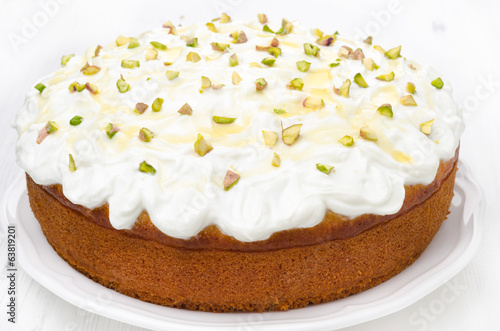 orange cake with Greek yogurt, honey and pistachios on a plate