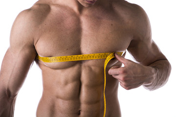 Muscular shirtless young man measuring chest with tape measure