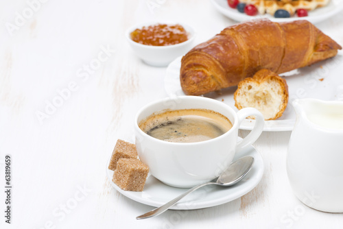 sweet breakfast with black coffee, croissants and orange jam