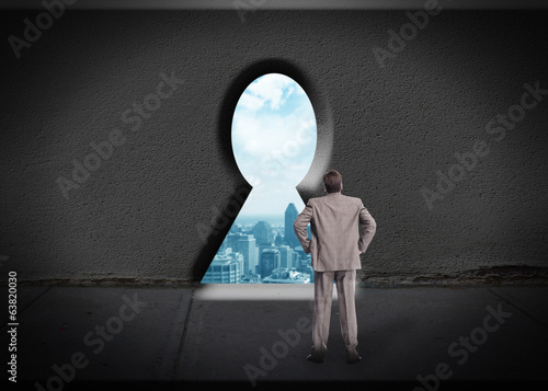 Businessman looking through keyhole.
