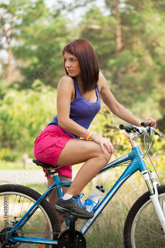 beauty girl on bike in summer day. Outdoors
