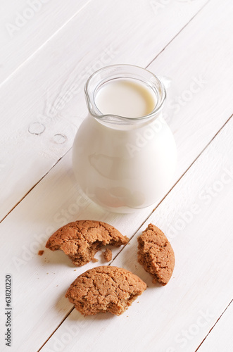 Milk in a glass jug and oatmeal cookies